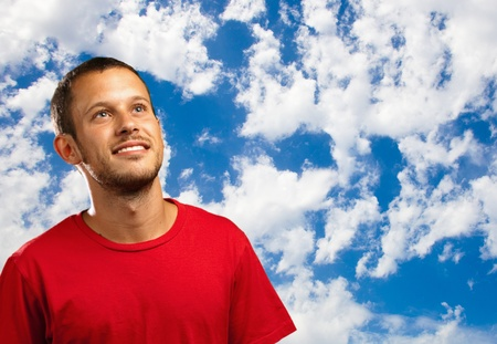 young man smiling and looking up against a sky background photo