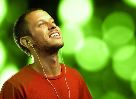man listening to music with earphones against a lights background photo