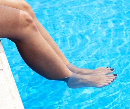 pies sexis: piernas de una mujer de belleza en el agua de la piscina Foto de archivo