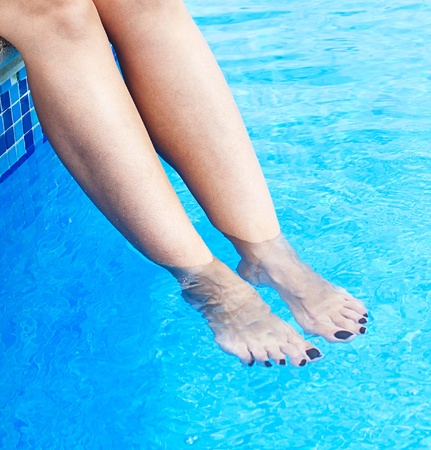 woman beauty legs in the water of pool photo