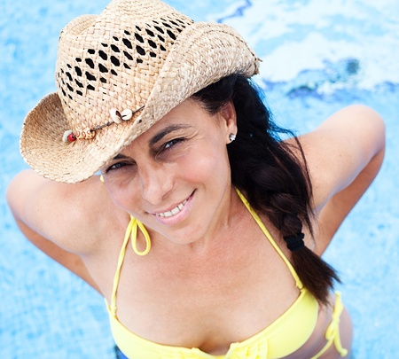 woman relaxing at pool with sunglasses and straw hat photo