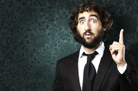 young business man pointing up against a grunge background Stock Photo - 10383296