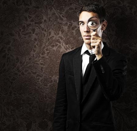 glass eye: Retrato de joven guapo mirando a trav�s de un vidrio de magniying contra una pared de grunge
