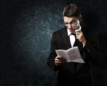 portrait of handsome young man reading a contract through a magnifying glass against a grunge background