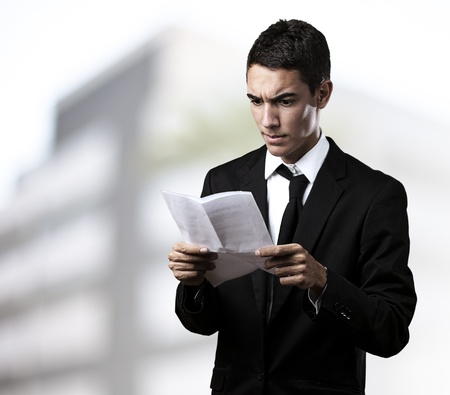 portrait of young business man reading contract in a house Stock Photo - 10383557