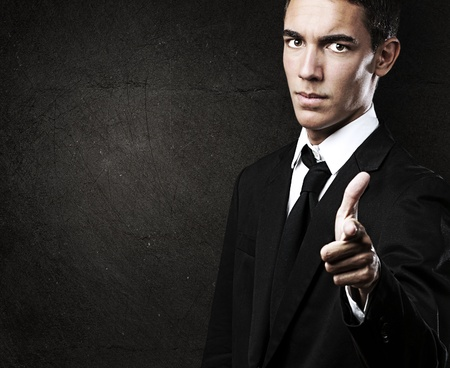 hispanic students: portrait of handsome young man pointing against a grunge background