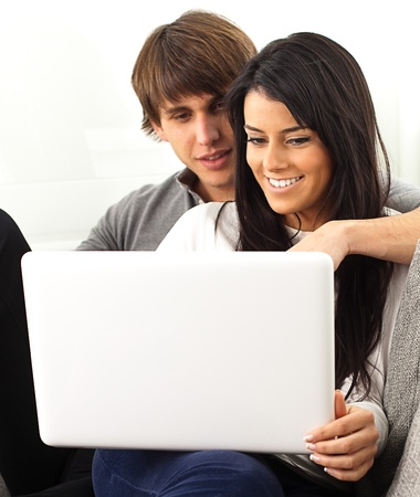 young couple playing with pc on white background photo