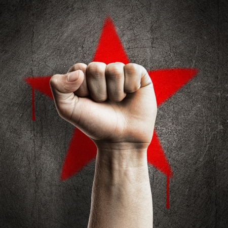 Vuist tegen een rode graffiti ster op een betonnen wand van grunge, vertegenwoordigen revolutie
