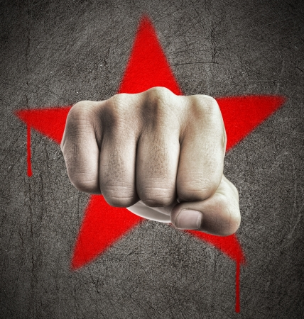 revolt: Fist against a red graffiti star on a grunge concrete wall, representing revolution Stock Photo