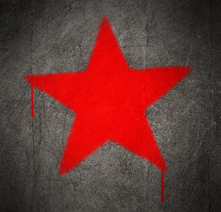 eroded: red star graffiti on a grunge concrete wall