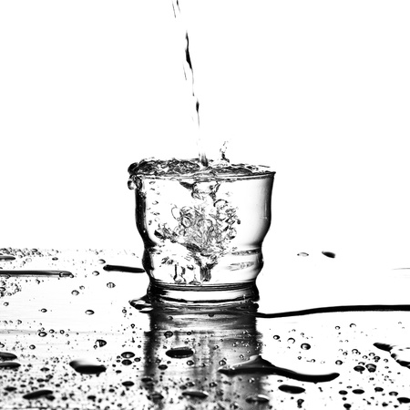 pouring water on glass on a white background photo