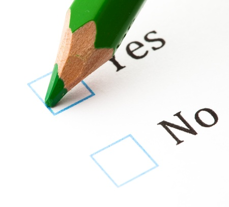 voting paper: questionnaire check boxes and green pencil, closeup
