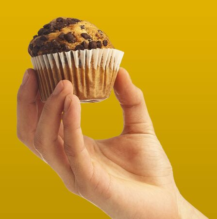 man holding a chocolate muffin on yellow background photo