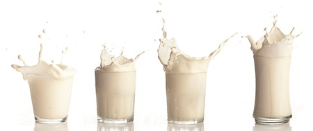 latte fresco: spruzzi di latte su un vetro su sfondo bianco Archivio Fotografico