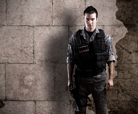 young armed soldier against a grunge background photo