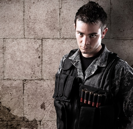 iraq war: young armed soldier against a grunge background