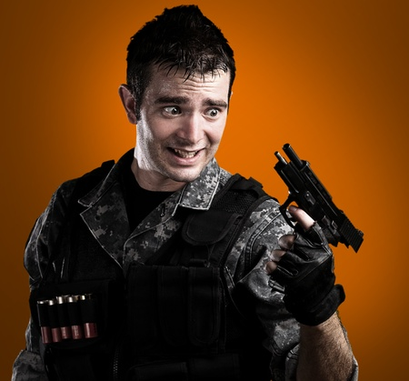 young soldier without ammunition of pistol on orange background photo