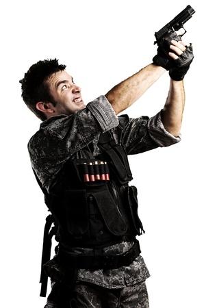 point and shoot: Retrato de joven soldado disparando con una pistola contra un fondo blanco