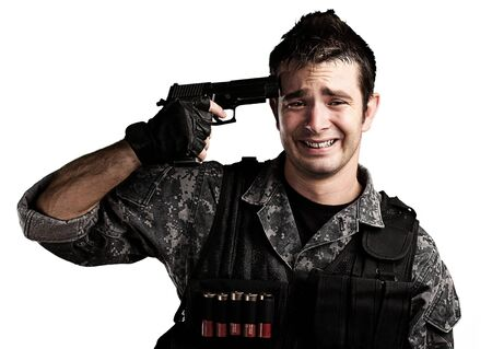 portrait of young soldier suiciding against a white background photo