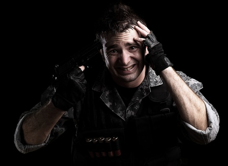 young soldier pointing himself on a black background photo