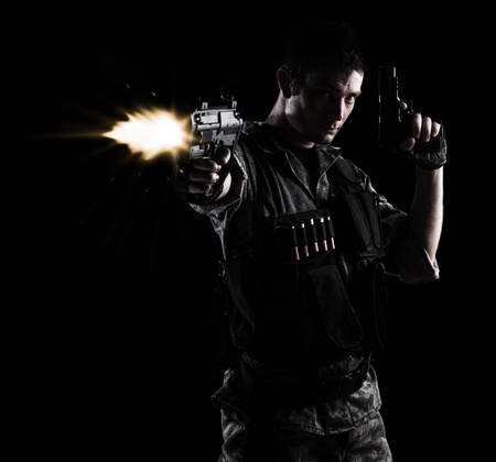 gun man: young soldier shooting with a pistol on a black background Stock Photo