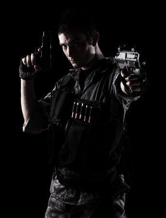 man holding gun: young soldier shooting with a pistol on a black background Stock Photo