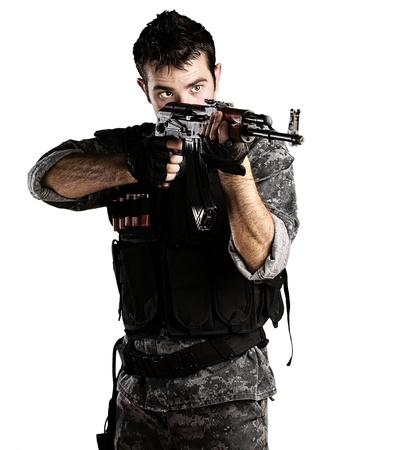 snajper: Portret młodego żołnierza, wskazując z karabinem na białym tle Zdjęcie Seryjne
