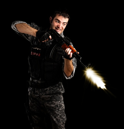 man holding gun: young soldier wearing urban camouflage shooting with a rifle on black background