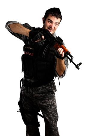 hombre disparando: joven soldado llevaba camuflaje urbano disparos con un rifle sobre fondo blanco Foto de archivo