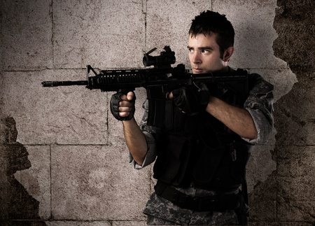 special agent: young soldier pointing a target against a grunge bricks wall Stock Photo