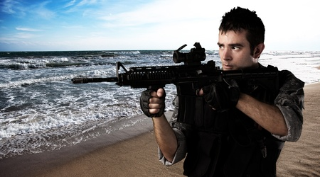 young soldier with rifle in the beach