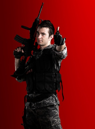 young soldier with urban camouflage and rifle on a red background photo
