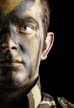 face guard: portrait of young soldier face with jungle camouflage paint against a black background Stock Photo