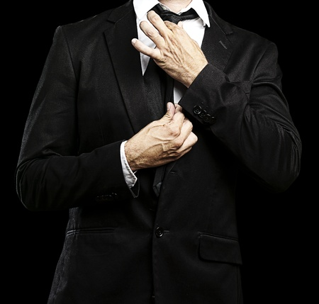 adjusting: young man adjusting his suit on a black background Stock Photo