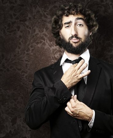 portrait of young man adjusting his suit against a grunge background photo