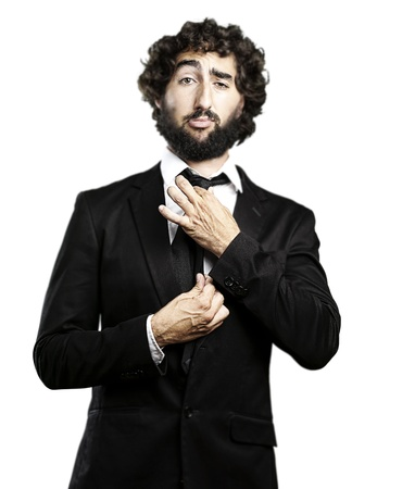 adjusting: portrait of young man adjusting his suit against a white background