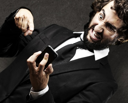 portrait of young business man angry with the new technologies against a grunge background photo