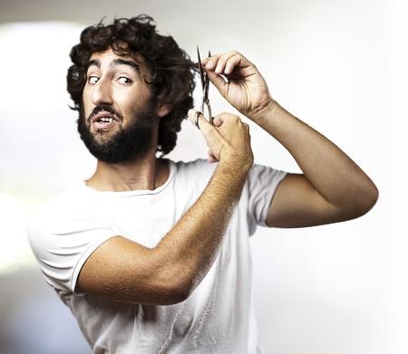 Portret van een jonge man, het snijden van het haar in een woonkamer Stockfoto