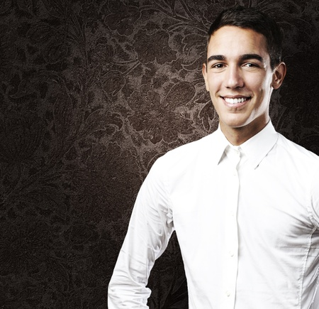 portrait of young man with a white shirt smiling against a vintage wall photo