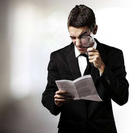 portrait of handsome young man reading a contract through a magnifying glass photo