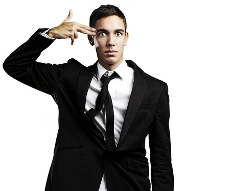 portrait of young man doing suicide symbol gesture against a black background Stock Photo - 10551106