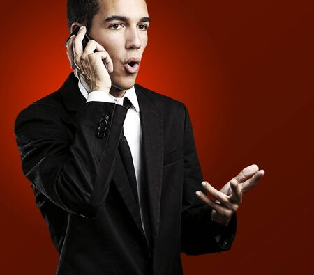 portrait of handsome young man talking on mobile against a red background Stock Photo - 10550394