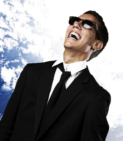 people laughing: portrait of young man laughing in suit and sunglasses against a blue sky background
