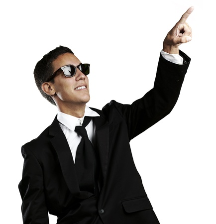 portrait of handsome young man with sunglasses pointing up against a white background photo