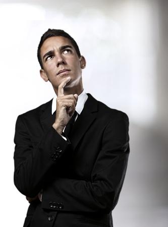 hombre pensando: retrato de joven hombre de negocios pensando en una casa