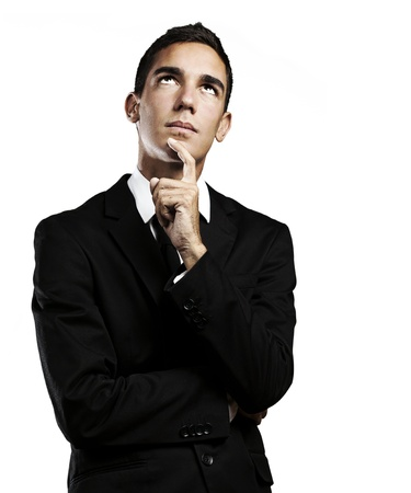 thoughful: portrait of thoughful young man wearing suit against a white background