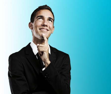 modern businessman: portrait of handsome young business man thinking and looking up against a blue background