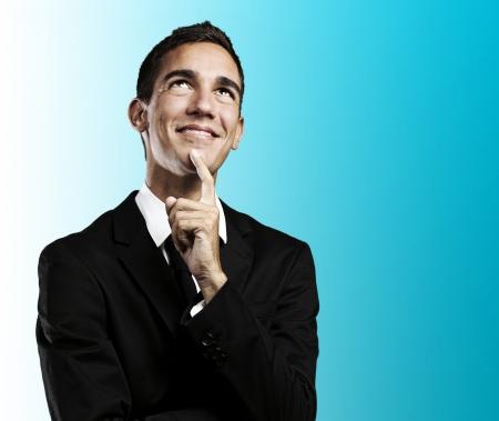 hombre pensando: Retrato de hombre de negocios joven guapo pensando y buscando contra un fondo azul