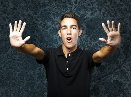 portrait of young man doing stop symbol against a vintage wall Stock Photo - 10545289