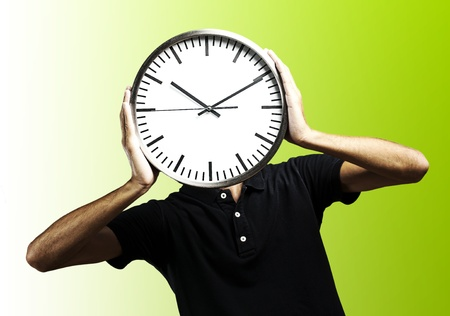 young man covering his face with a clock over green background photo